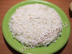 Половину риса выложить на дно тарелки ровным слоем.